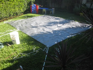 Tarpaulin laid out with pegs, poles and guy ropes ready for raising