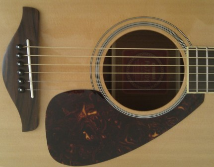 Saddle, bridge, sound hole and pick guard of the Yamaha FG720S acoustic guitar